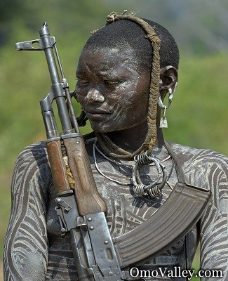 A member of th Mursi tribe with an AK 47